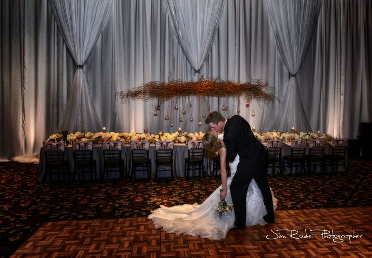 Wedding couple kisses in front of Elegant Draping Lighting for Dallas Weddings